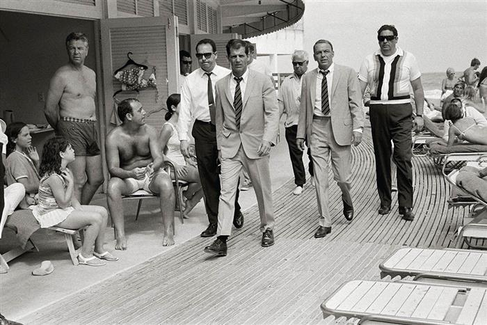 'Frank Sinatra on the boardwalk at Miami Beach Florida, accompanied by stand-in and bodyguards, 1968