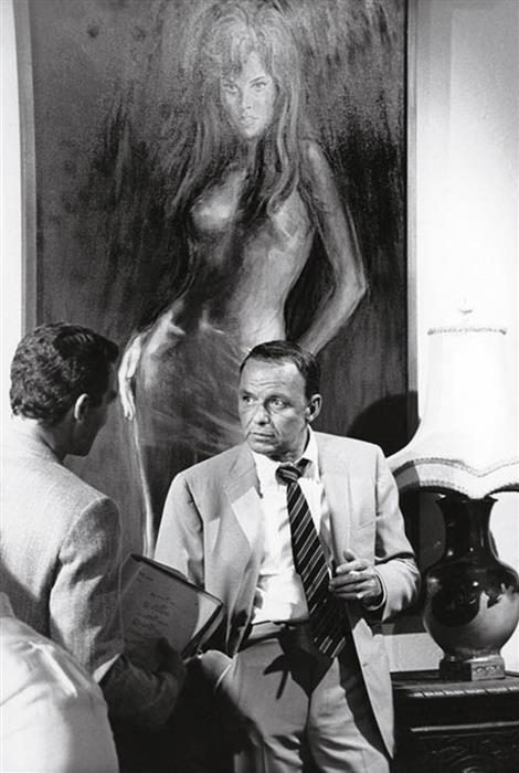 Frank Sinatra standing beneath a portrait of Raquel Welch in Miami, 1968